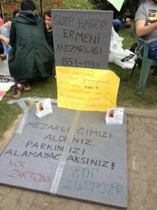 """Silhouette en carton d'une tombe arménienne. On y lit : Cimetière arménien Surp Hagop. 1551-1939: """"Vous avez pris notre cimetière, mais vous ne nous prendrez pas notre parc""""."""